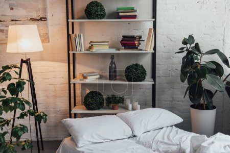 Photo for Modern interior design of bedroom with rack, plants, lamp, bed and brick wall - Royalty Free Image