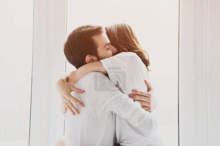 Foto de Hermosa joven pareja abrazándose apasionadamente con la luz solar sobre fondo - Imagen libre de derechos