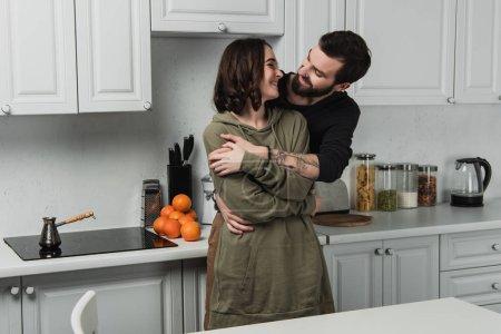 Photo pour Beau jeune couple étreindre et souriant dans kithchen pendant le petit déjeuner - image libre de droit