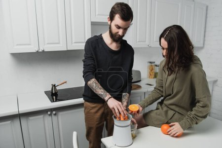 Photo for Beautiful young couple preparing orange juice during breakfast in kitchen - Royalty Free Image