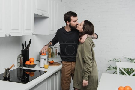 Photo for Beautiful young couple making orange juice, hugging and kissing during breakfast in kitchen - Royalty Free Image