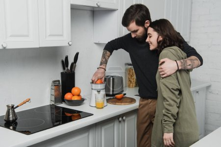 Photo for Beautiful young couple making orange juice and hugging during breakfast in kitchen - Royalty Free Image