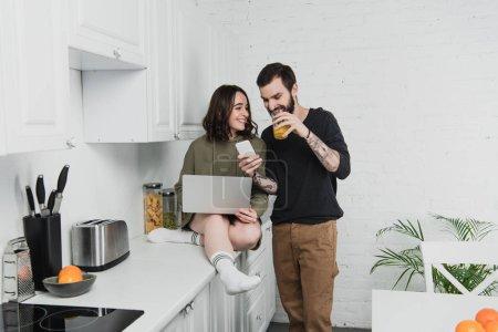 Photo pour Homme boire du jus et en utilisant smartphone tout en souriant femme en utilisant un ordinateur portable pendant le petit déjeuner dans la cuisine - image libre de droit