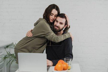 Photo pour Beau couple heureux câlin tout en étant assis à la table avec ordinateur portable et oranges pendant le petit déjeuner dans la cuisine - image libre de droit