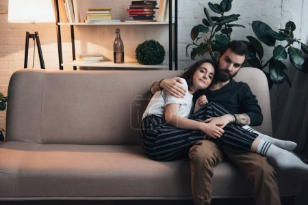 Photo for Beautiful young couple embracing while sitting on couch in living room with copy space - Royalty Free Image