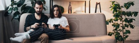 Photo for Beautiful surprised young couple sitting on couch with joysticks and playing video game in living room - Royalty Free Image