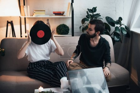 Foto de Mujer joven que cubre la cara con disco de vinilo mientras está sentado en el sofá con el hombre en la sala de estar - Imagen libre de derechos