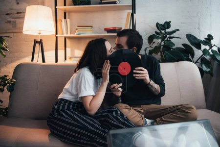Photo for Beautiful young couple covering faces with vinyl record and kissing while sitting on couch in living room - Royalty Free Image