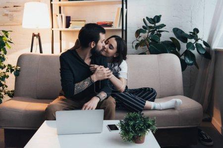 Foto de Hermosa pareja jóvenes sentados en el sofá y besándose junto a la laptop y smartphone en mesa de salón - Imagen libre de derechos