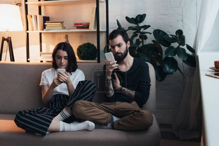Photo for Focused young couple sitting on couch and using smartphones in living room - Royalty Free Image
