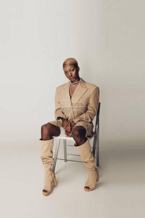Foto de Fashionable african american woman in elegant beige jacket sitting on chair on grey - Imagen libre de derechos