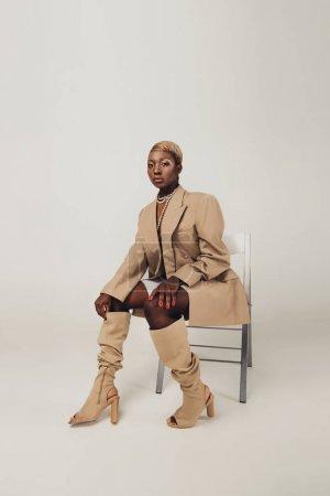 Photo pour Fashion Shoot avec la femme américaine africaine dans la veste beige s'asseyant sur la présidence sur le gris - image libre de droit