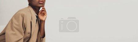 Photo pour Vue recadrée de femme américaine africaine à la mode dans la veste beige d'isolement sur le gris - image libre de droit