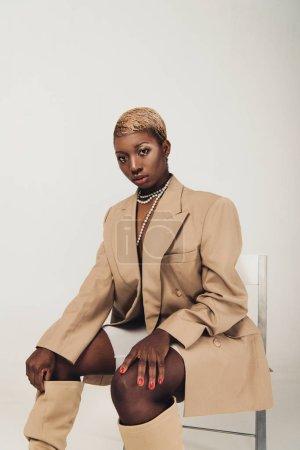 Photo pour Femme américaine africaine à la mode dans la veste et le collier beige s'asseyant sur la présidence d'isolement sur le gris - image libre de droit