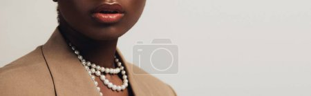 Photo for Cropped view of african american woman in beige jacket and necklace isolated on grey - Royalty Free Image