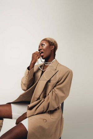 Photo for Trendy african american woman in beige jacket and necklace sitting on chair isolated on grey - Royalty Free Image