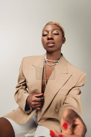 fashionable african american woman in necklace and beige jacket sitting on chair isolated on grey