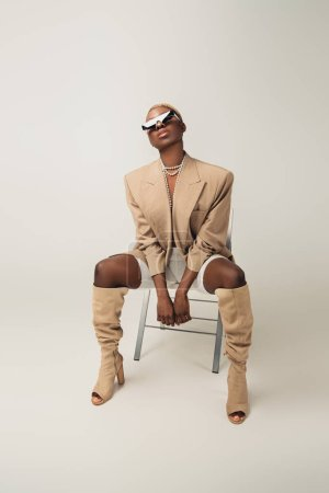 Photo for Fashionable african american woman in trendy sunglasses sitting on chair on grey - Royalty Free Image