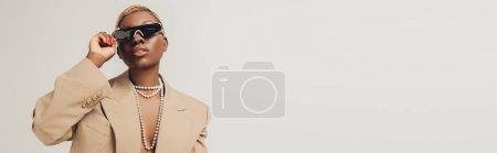 Photo pour Fille américaine africaine à la mode posant dans des lunettes de soleil et veste beige à la mode d'isolement sur le gris - image libre de droit