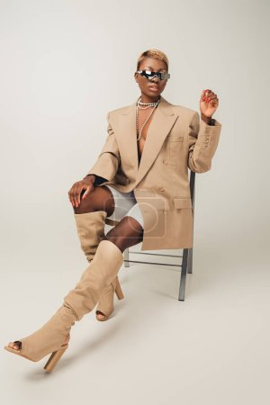 Photo for Attractive african american woman in sunglasses and beige jacket sitting on chair on grey - Royalty Free Image