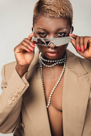 Photo pour Fashionable elegant african american girl posing in sunglasses and beige jacket isolated on grey - image libre de droit