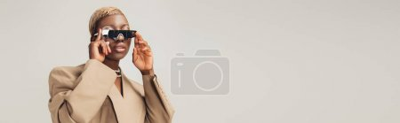 Photo for Fashionable african american woman posing in sunglasses and beige jacket isolated on grey - Royalty Free Image