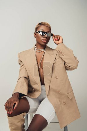 Photo pour Femme américaine africaine élégante dans des lunettes de soleil et la veste beige élégante s'asseyant sur la présidence sur le gris - image libre de droit
