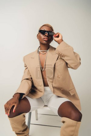 Photo for African american woman in sunglasses and fashionable jacket sitting on chair on grey - Royalty Free Image
