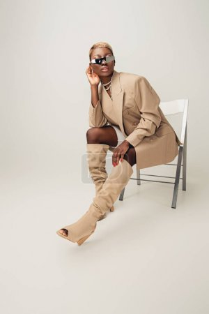 Photo pour Young african american woman in sunglasses and beige jacket sitting on chair on grey - image libre de droit