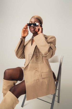 Photo pour Modèle américain africain à la mode dans des lunettes de soleil et veste beige s'asseyant sur la chaise sur le gris - image libre de droit