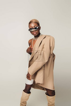 Photo for Naked african american girl posing in beige jacket isolated on grey - Royalty Free Image