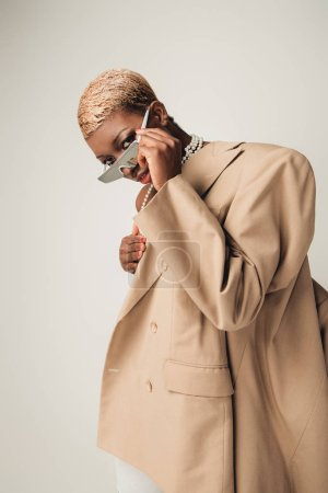 Photo for Stylish african american girl with short hair posing in sunglasses and beige jacket isolated on grey - Royalty Free Image