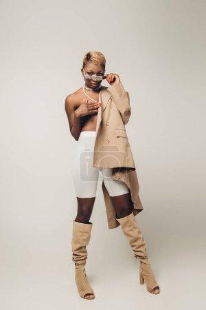 Photo pour Fille américaine africaine nue posant dans des lunettes de soleil et la veste beige d'isolement sur le gris - image libre de droit