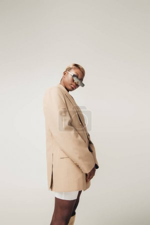 Photo for African american girl posing in sunglasses and beige jacket isolated on grey - Royalty Free Image