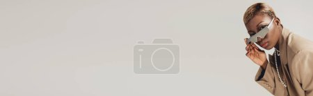 Photo for Trendy african american girl posing in sunglasses and beige jacket isolated on grey - Royalty Free Image