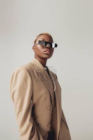 Photo pour Fille américaine africaine à la mode posant dans des lunettes de soleil et veste beige d'isolement sur le gris - image libre de droit