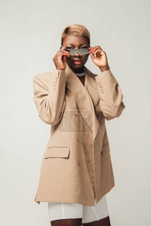 Photo for Stylish african american girl posing in sunglasses and elegant beige jacket isolated on grey - Royalty Free Image