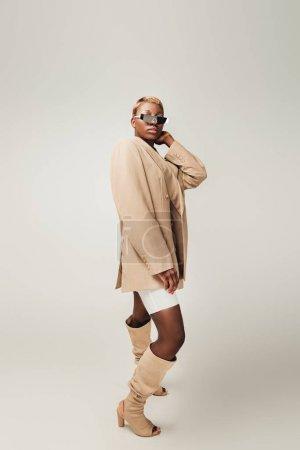 Photo pour Fille américaine africaine à la mode posant dans des lunettes de soleil et veste beige sur le gris - image libre de droit