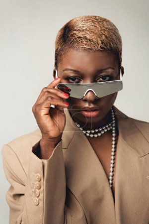 Photo for Portrait of stylish african american girl in sunglasses and beige jacket isolated on grey - Royalty Free Image
