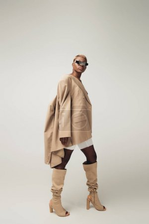 stylish young african american girl posing in sunglasses and beige jacket on grey