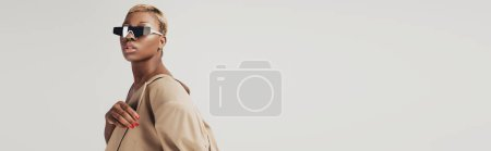 Photo for Beautiful african american girl posing in sunglasses and trendy beige jacket isolated on grey - Royalty Free Image