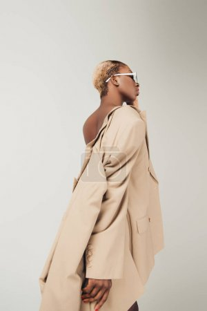 Photo for African american girl posing in sunglasses and fashionable beige jacket isolated on grey - Royalty Free Image