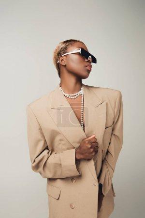 Photo pour Fille américaine africaine élégante posant dans des lunettes de soleil et la veste beige élégante d'isolement sur le gris - image libre de droit
