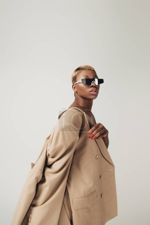 Photo for Beautiful stylish african american girl posing in sunglasses and beige jacket isolated on grey - Royalty Free Image