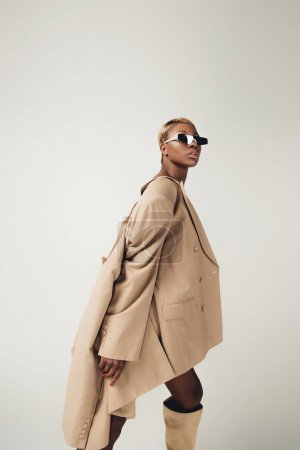 attractive african american girl posing in sunglasses and beige jacket isolated on grey