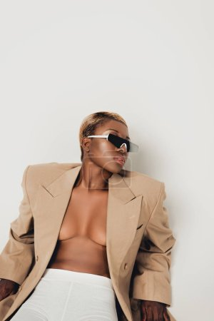 Photo for Stylish african american girl posing in sunglasses and beige jacket isolated on grey - Royalty Free Image