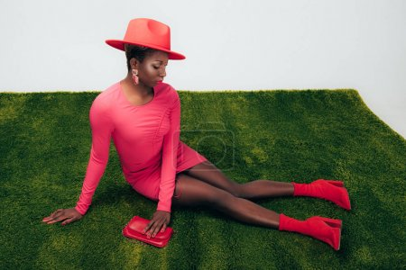 Photo pour Femme américaine africaine dans la robe et le chapeau roses posant avec le sac sur l'herbe verte - image libre de droit