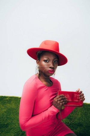 Photo pour Femme américaine africaine élégante dans la robe et le chapeau roses posant avec le sac sur l'herbe verte - image libre de droit