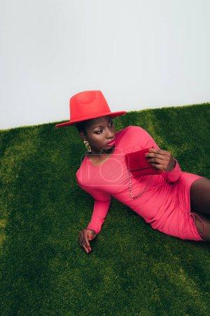 Photo pour Fashion Shoot avec la femme américaine africaine dans la robe et le chapeau roses posant avec le sac sur l'herbe verte - image libre de droit