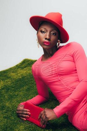 Photo pour Femme américaine africaine à la mode dans la robe et le chapeau roses posant avec le sac sur l'herbe verte - image libre de droit